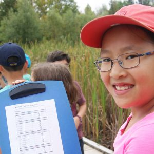 A student holds up a clipboard while standing with other students on the boardwalk over a wetland at Terra Cotta Conservation Area.