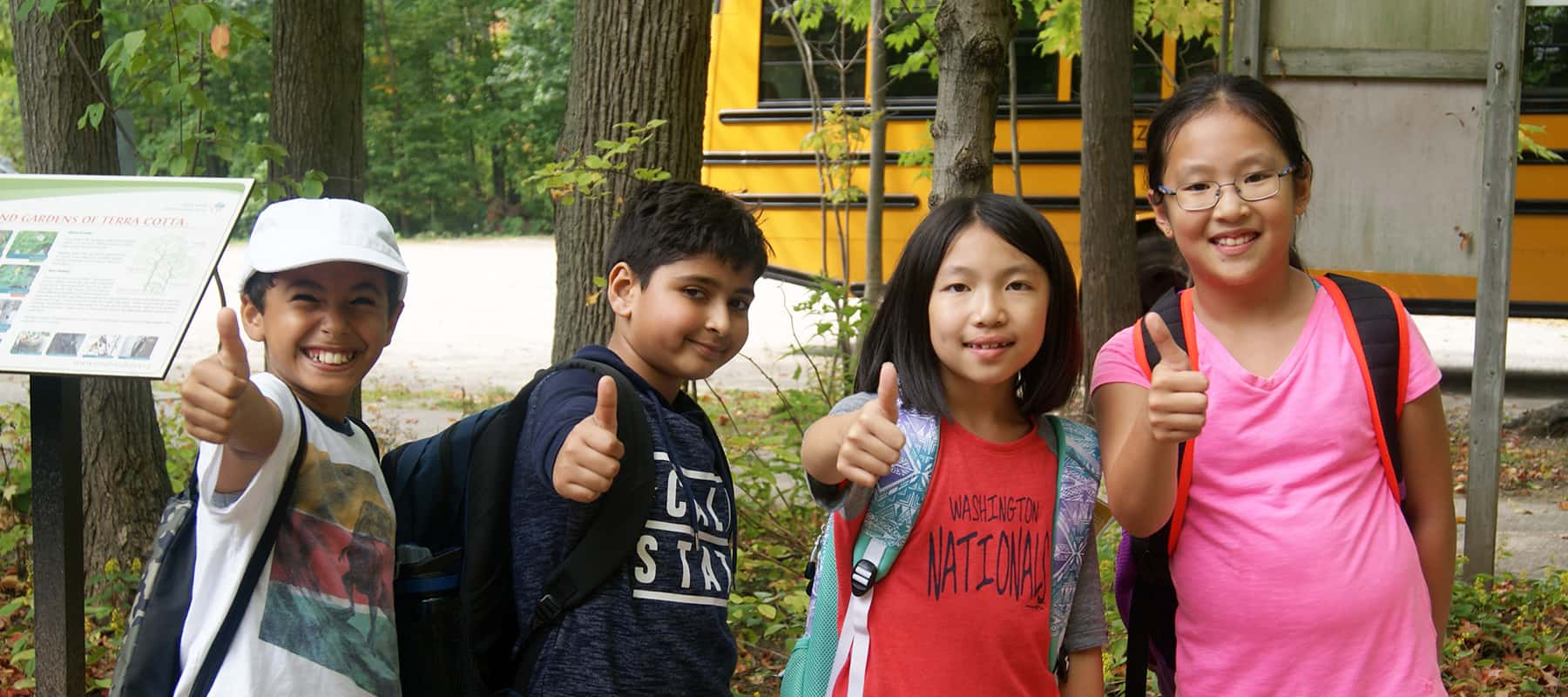 Four young children standing outside the Education Centre at Terra Cotta, in front of a school bus, giving thumbs ups.