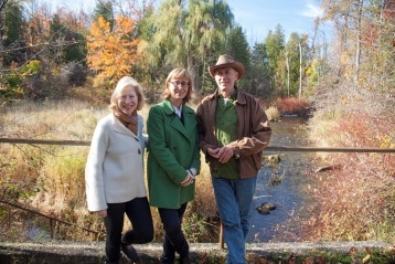Family stands on bridge overlooking a stream