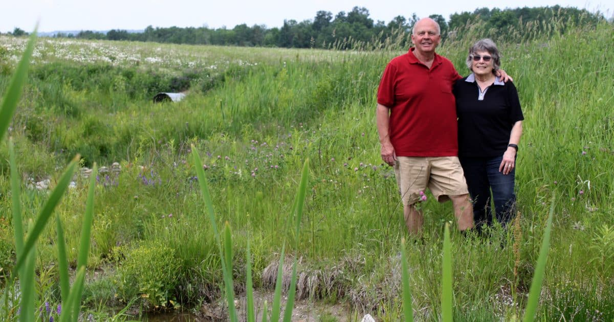 Two landowners stand by a restored stream