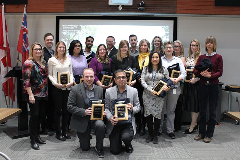 A large group of staff members pose for a photo with their award