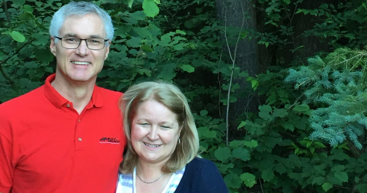 Two landowners stand in front a forest on their property