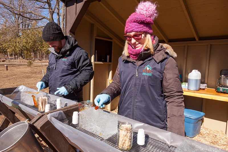 Two staff members in winter clothes prepare maple syrup samples frozen on sticks for park visitors.