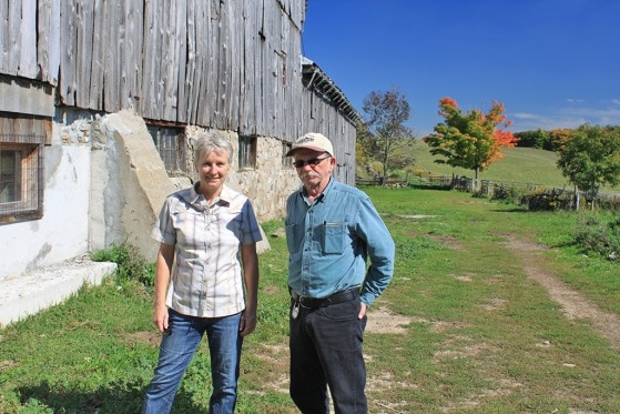 Farmer stands in front of barn with friend