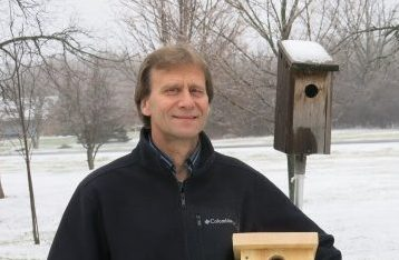 Landowner posing with bird nesting boxes on their property