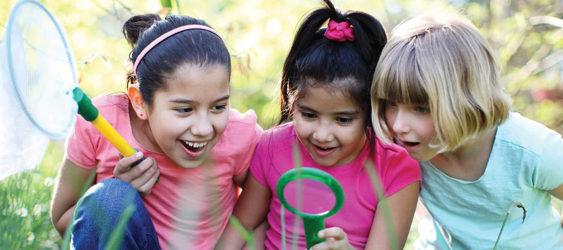 Three young girls crouch down to look closely at something in nature with a magnifying glass.