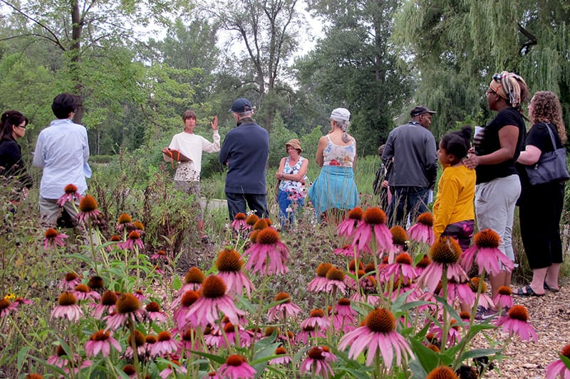 A group of people surrounding a CVC staff member who is describing the garden around them.