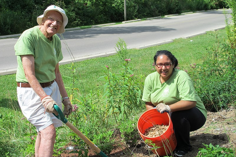 Two adults planting together in a garden - one person has a bucket, the other person has a shovel.