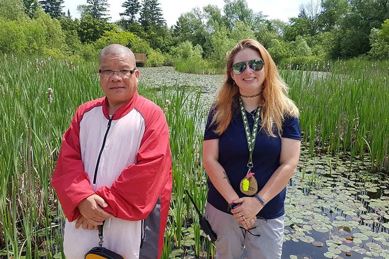 Two people standing in front of wetland area at Terra Cotta.