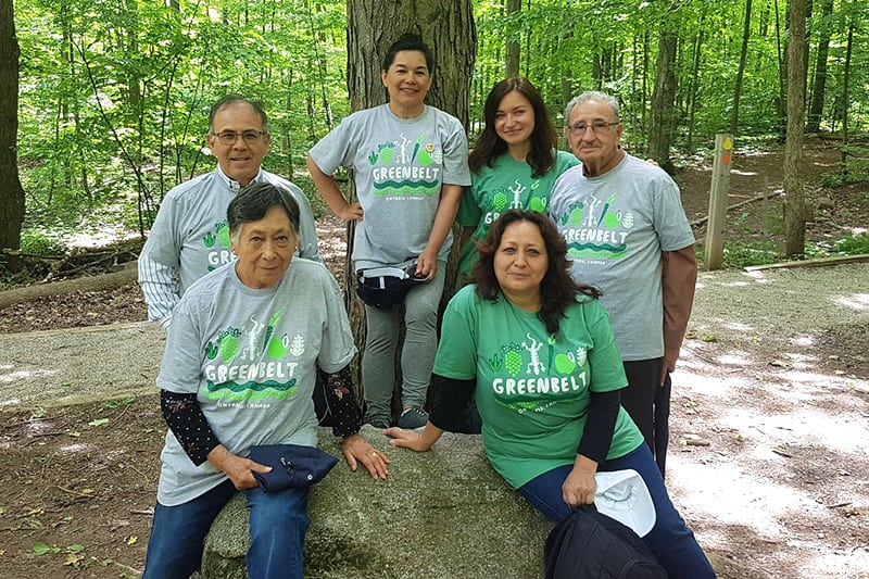 Six people wearing Greenbelt t-shirts posing for a photo on a large rock in the forest.