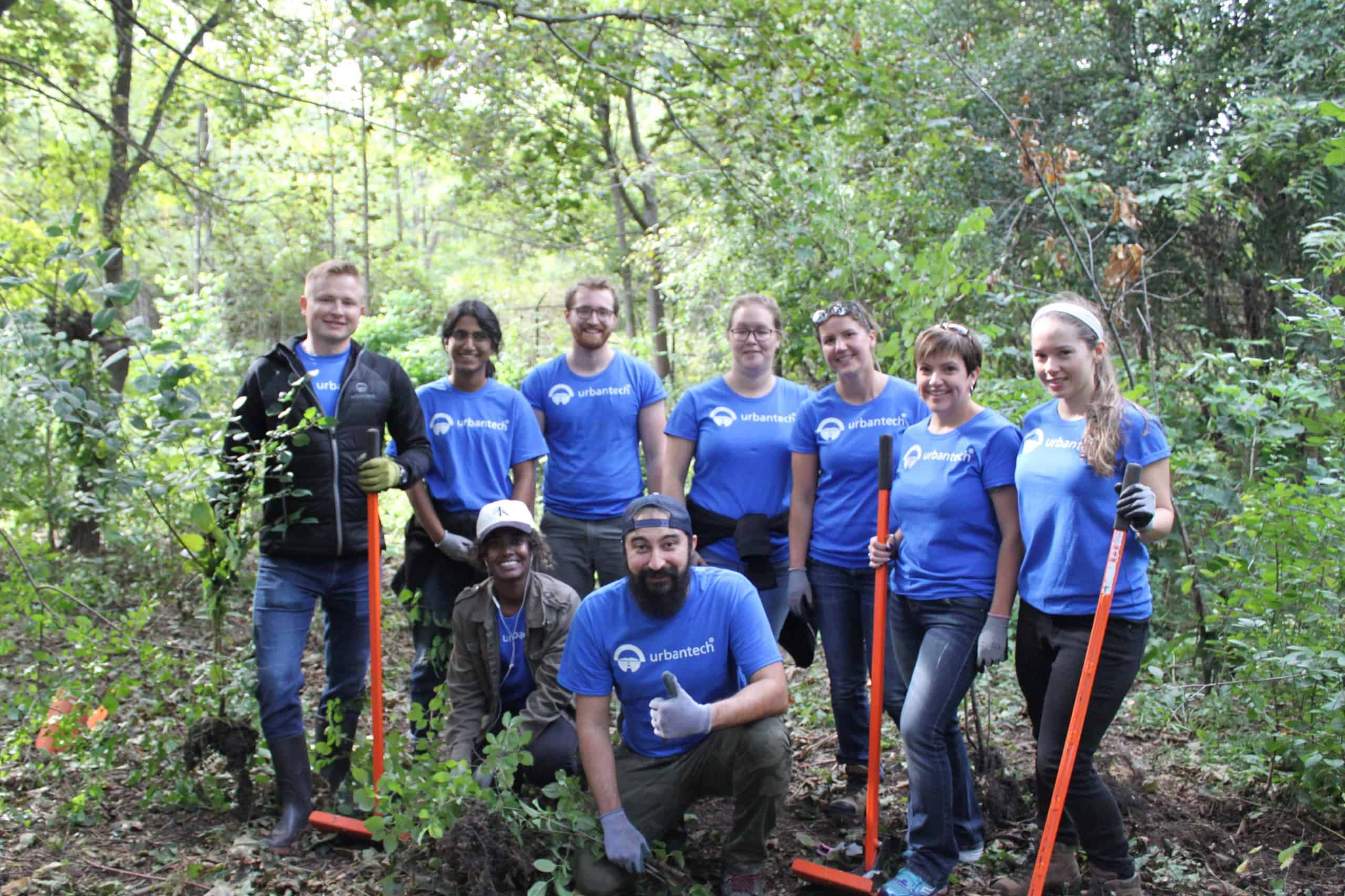a group of people standing in the forest with hand tools removing invasive species