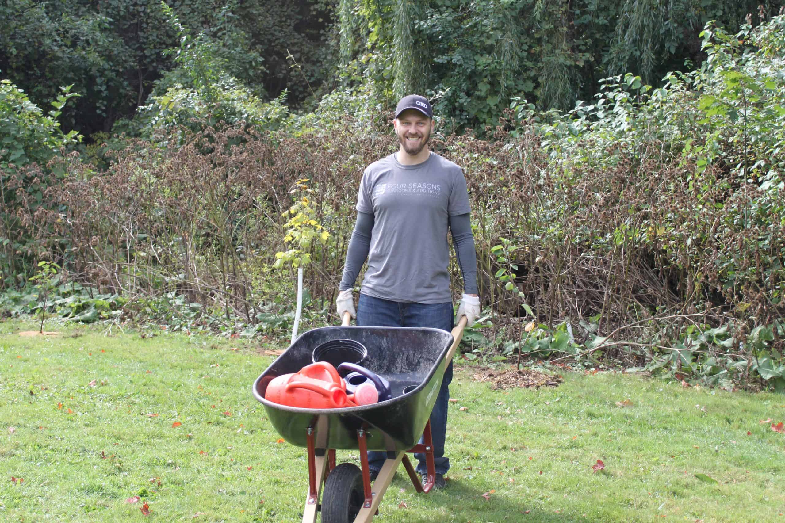 a person holding a wheelbarrow smiling at the camera