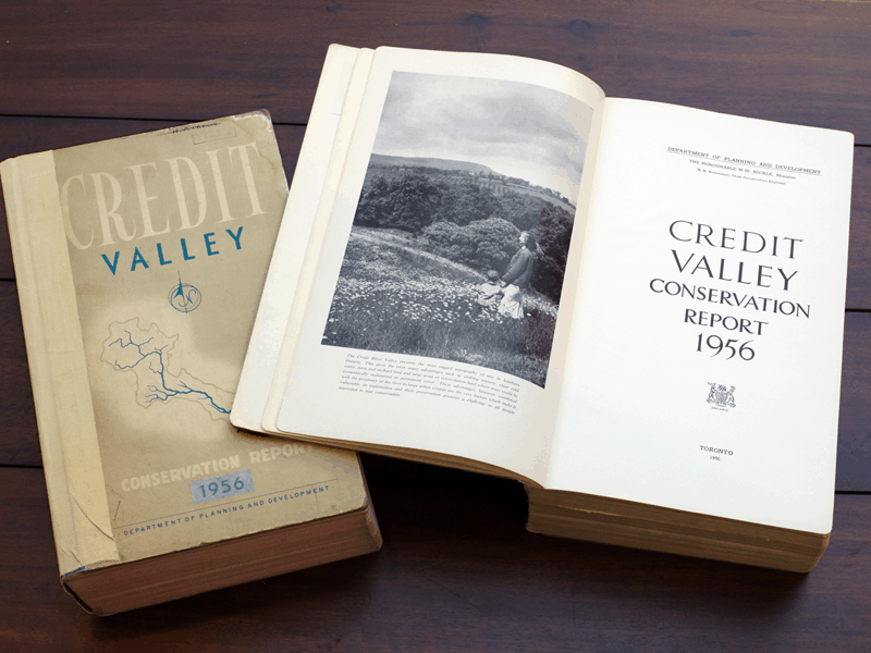 Two copies of the Credit Valley Conservation Report, 1956, on a table, one closed and one open to show the inside cover.