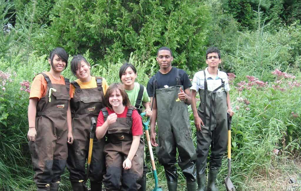 Group of teens with shovels and wearing hip waders doing stream restoration.