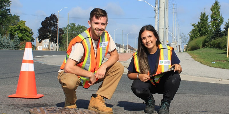 Two staff members wearing safety vests and work clothes squat down to pose for the camera on a city road.