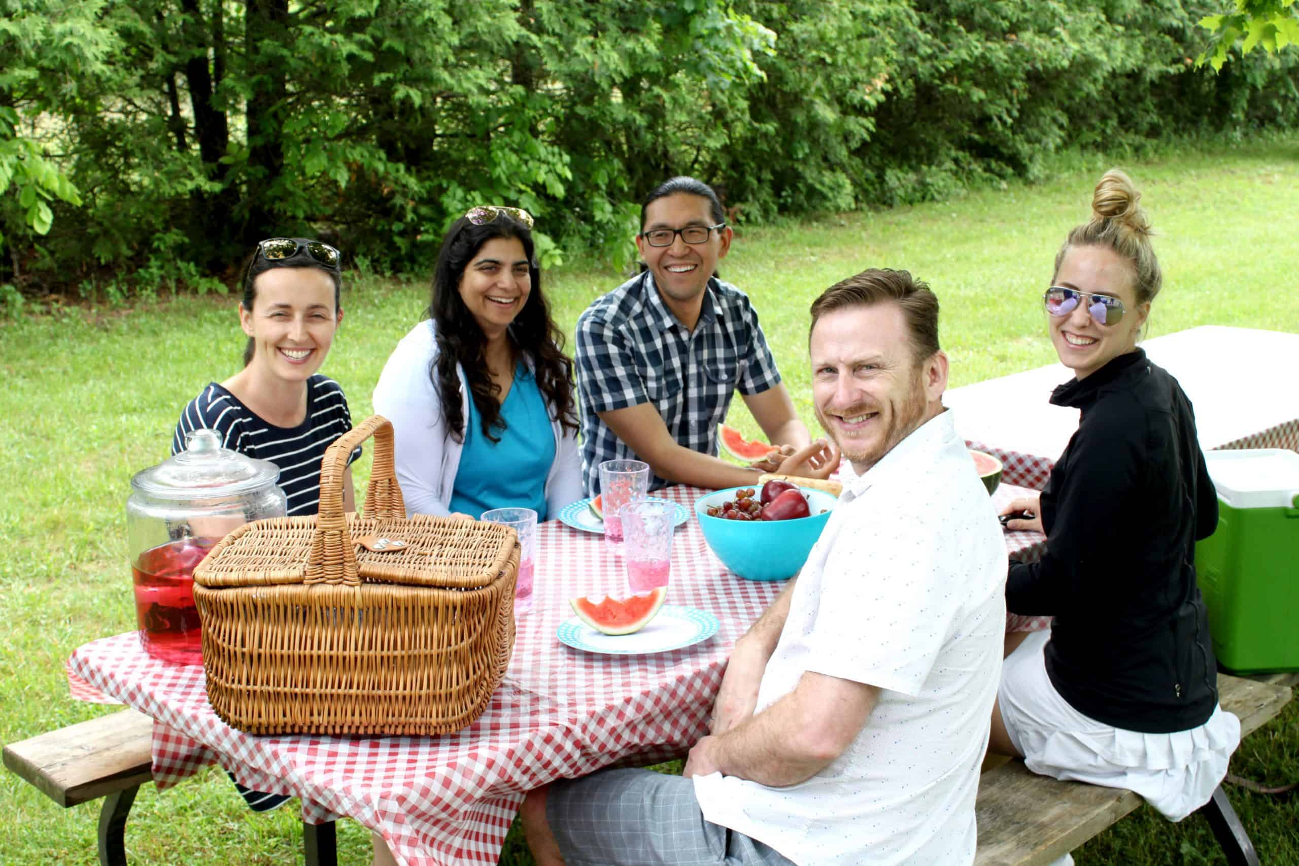 CVC staff sitting at a picnic table outdoors eating their lunch.