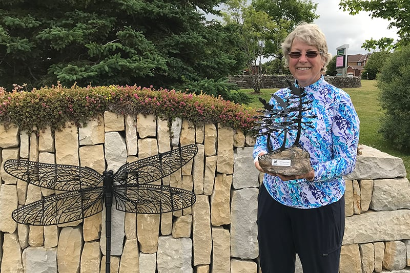 Lynn Sinclair posing with her award in front of a half wall outside with a large dragonfly decoration on it.