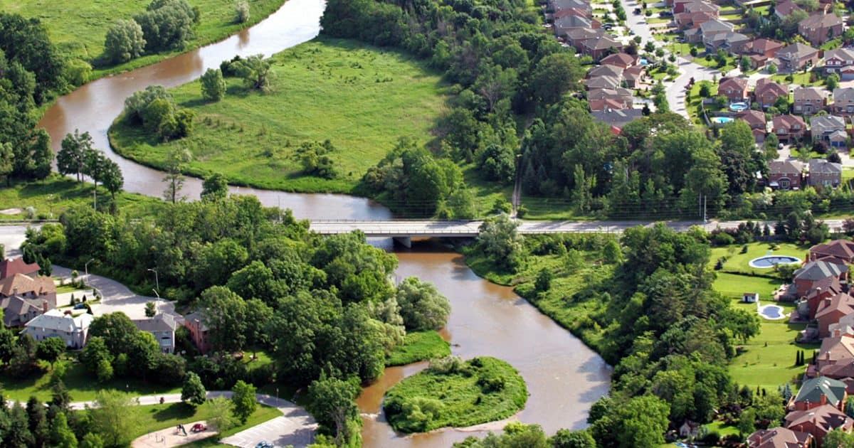 An aerial view of the Credit River as it winds between areas of greenspace and development.