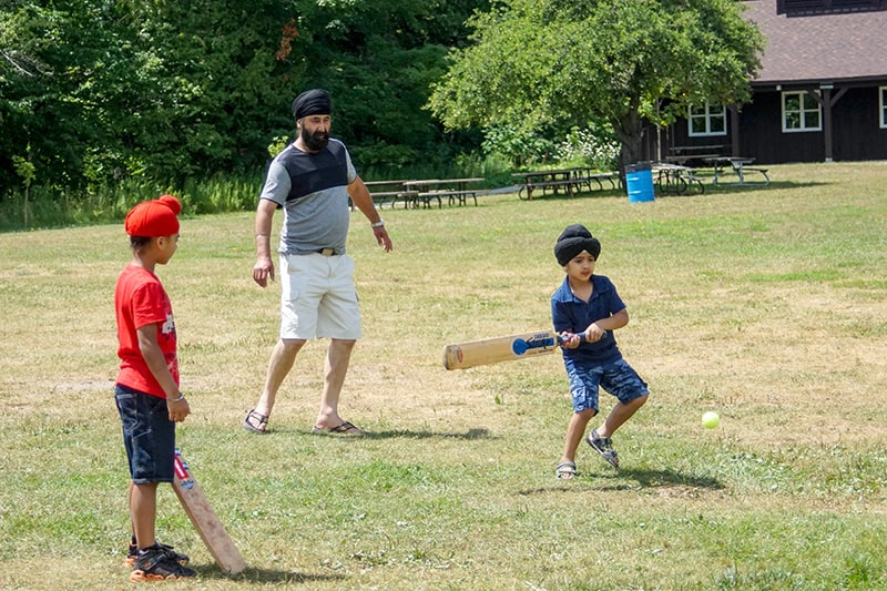 A young child swings a cricket bat while playing with family at a picnic.