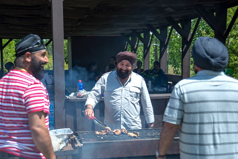 Family members gather around a barbecue, preparing food at a picnic.