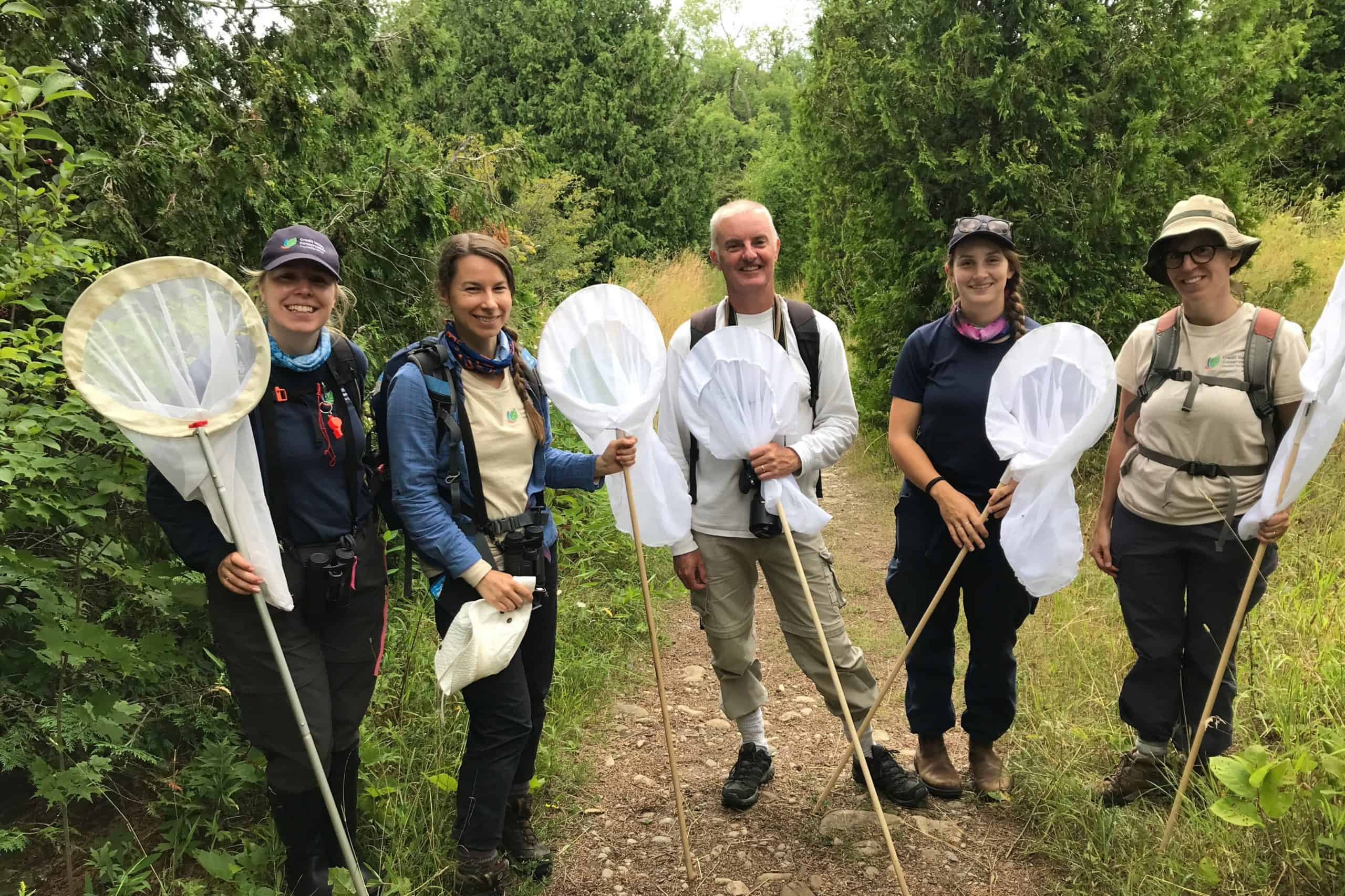 five people with butterfly nets standing on a trail with trees behind them