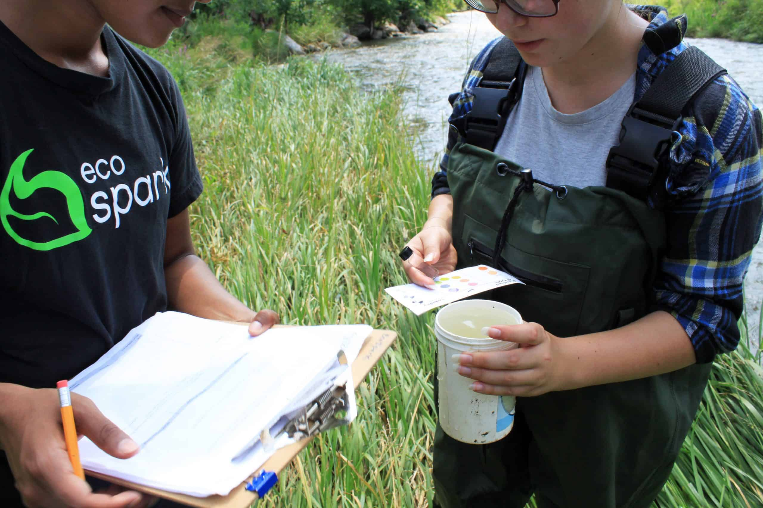 two teens holding a clipboard and monitoring equipment checking water quality in the stream behind them
