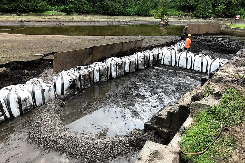 A picture containing outdoor, ground, soil and meter bag around a pond that where sediment is being removed