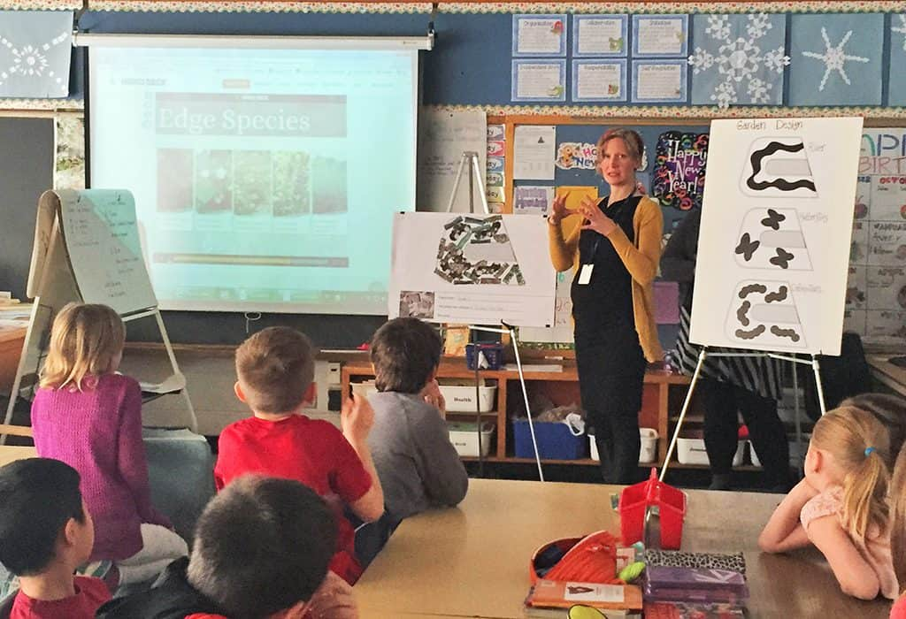 A CVC educator teaching children in a classroom setting with a presentation and boards.