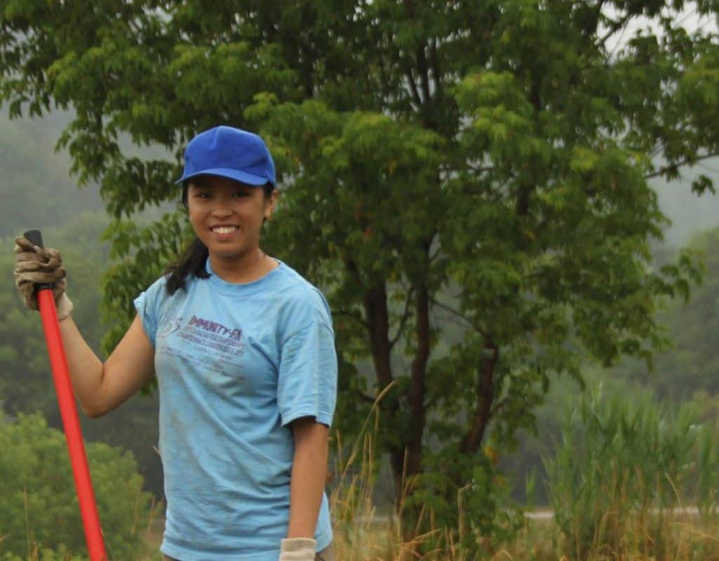 Teenager smiling and holding a shovel in a forest.