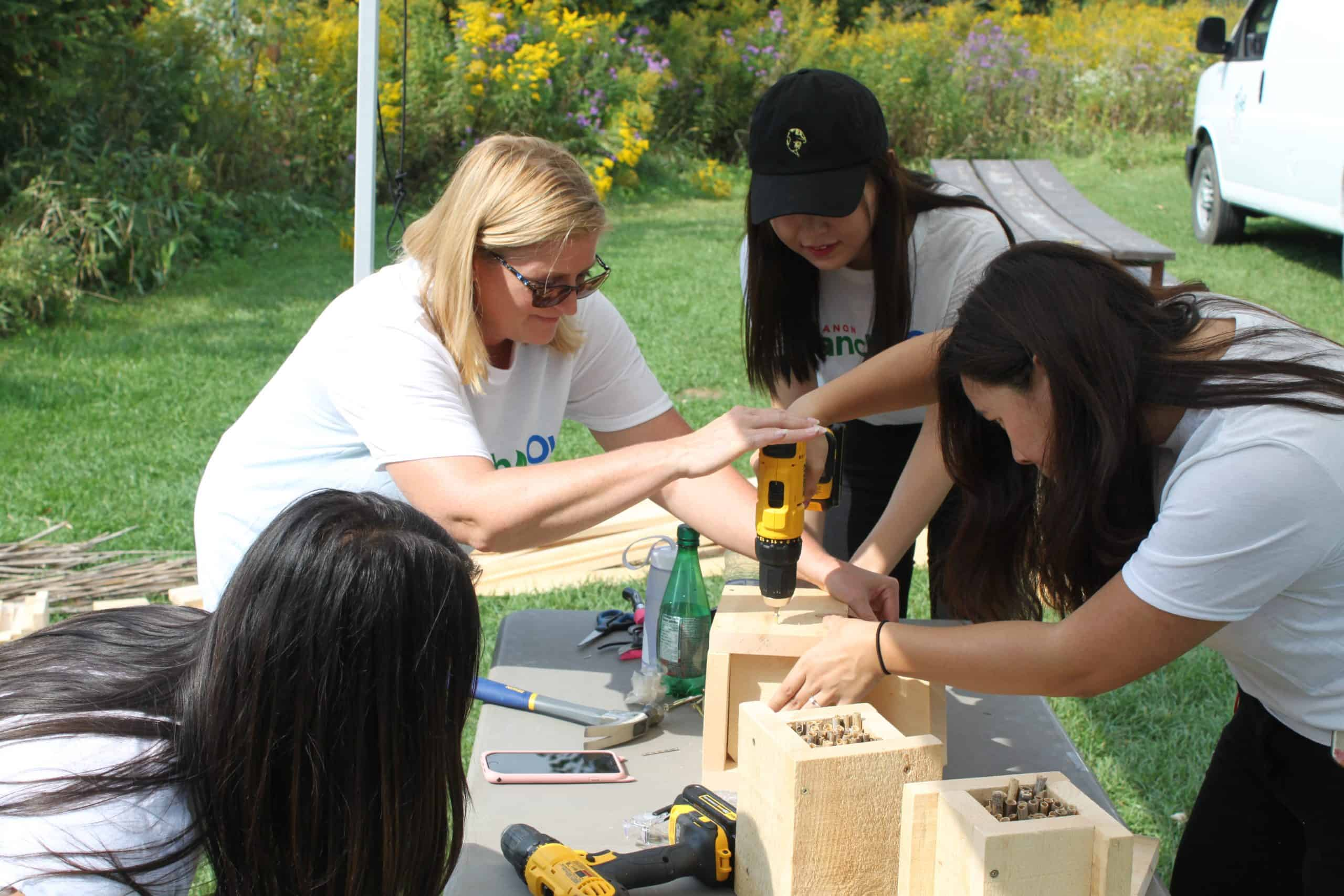 a group of people working at a table outdoors with a drill building habitat boxes