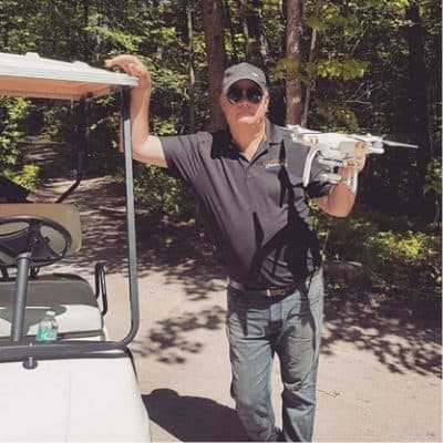 Darren Clark posing with a drone in his hand.