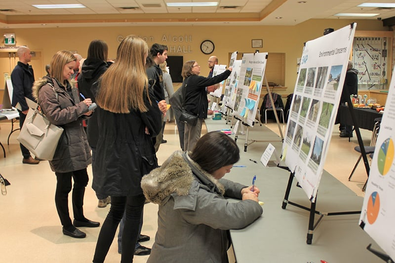 Residents look at poster boards at an open house