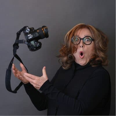 A playful portrait of Pamela Bell tossing her camera in the air.