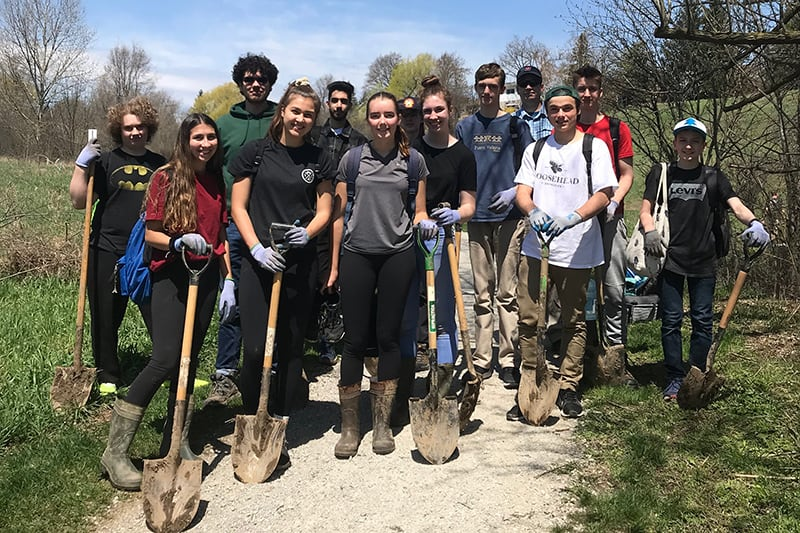 Youth volunteers holding shovels