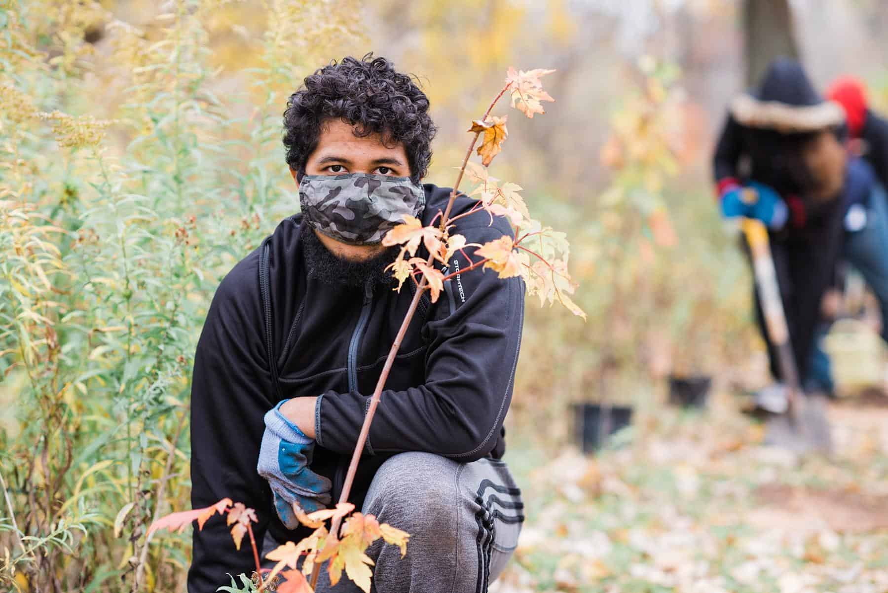 a student wearing work gloves and a mask kneeling behind a sapling they planted with other students working in the background