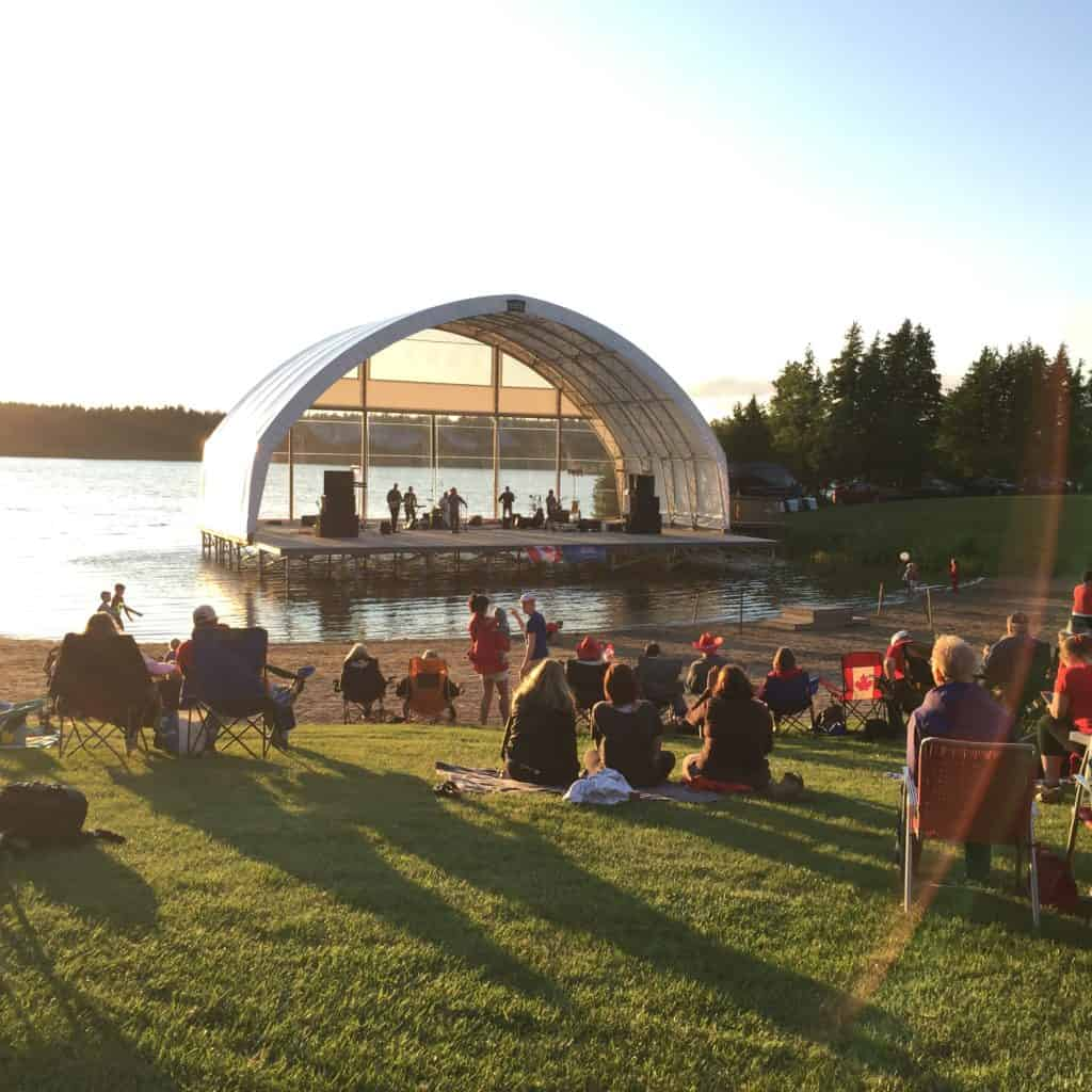 People sitting in front of an ampthitheatre with a band playing on the stage and water in the background
