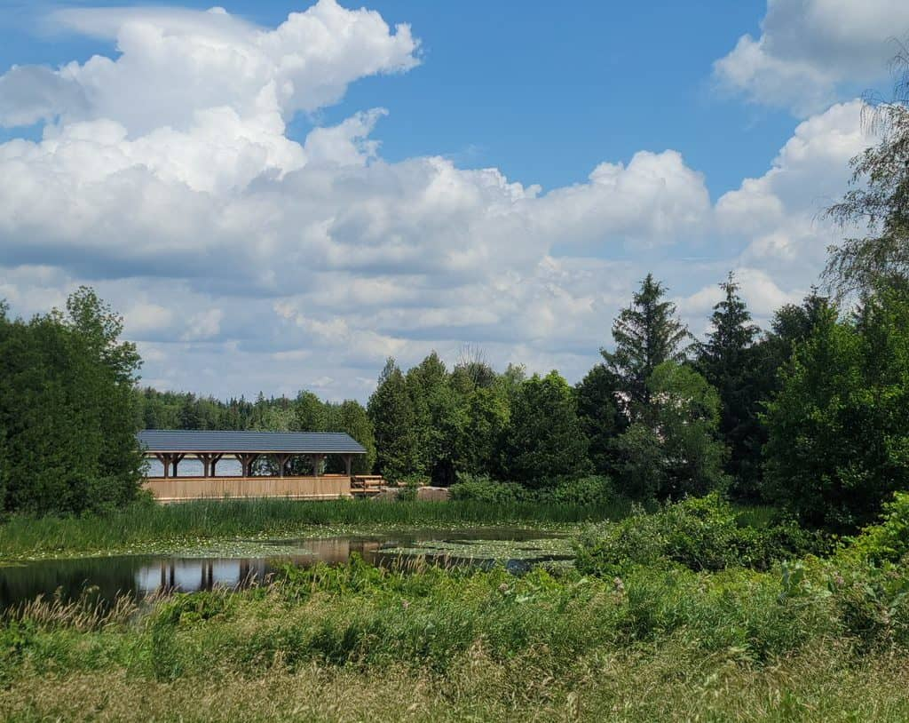 A covered bridge in the background with trees and water around it. Blue sky with fluffy clouds in the background